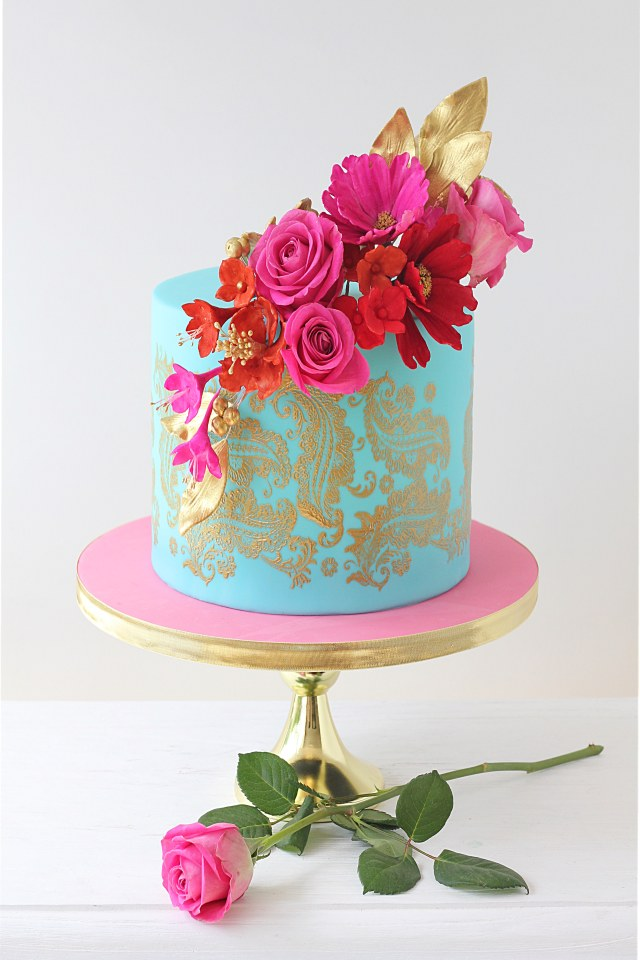 Turquoise coloured single tier celebration cake decorated with gold paisley design and dark pink and red flowers