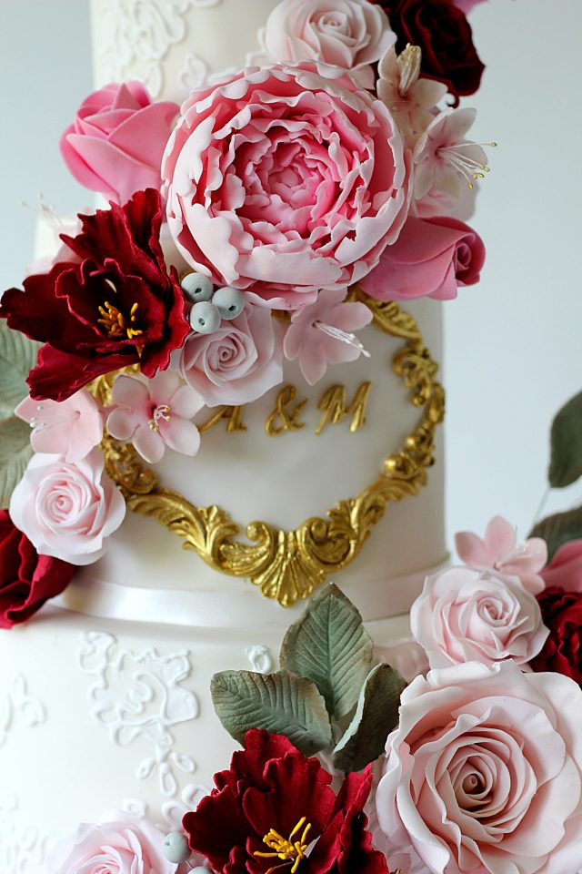 white four tier wedding cake with lace a wrap around cascades of pink and red sugar flowers