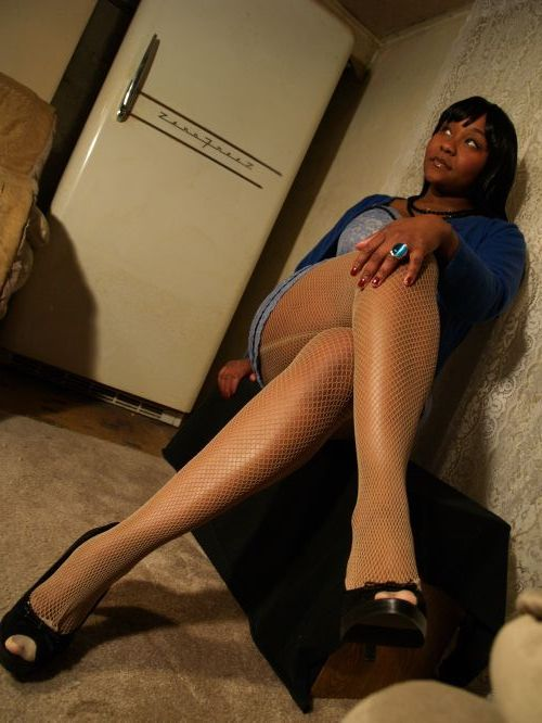 Sophia in a blue reconstructed lingerie dress and blue sweater with nude fishnets and black heels. Modeling.