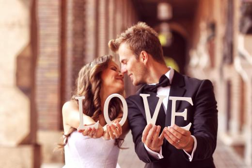 45822623 - beautiful bride and groom kissing and holding love letters
