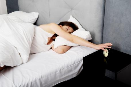 38775515 - tired and sleepy woman switches off alarm clock.