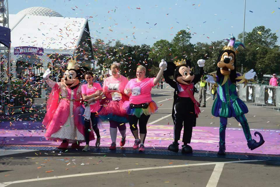 3 Sophie and Madigan Team Runners crossing the finish line arm and arm with Mickey Minnie and Goofy at the Princess Half Marathon