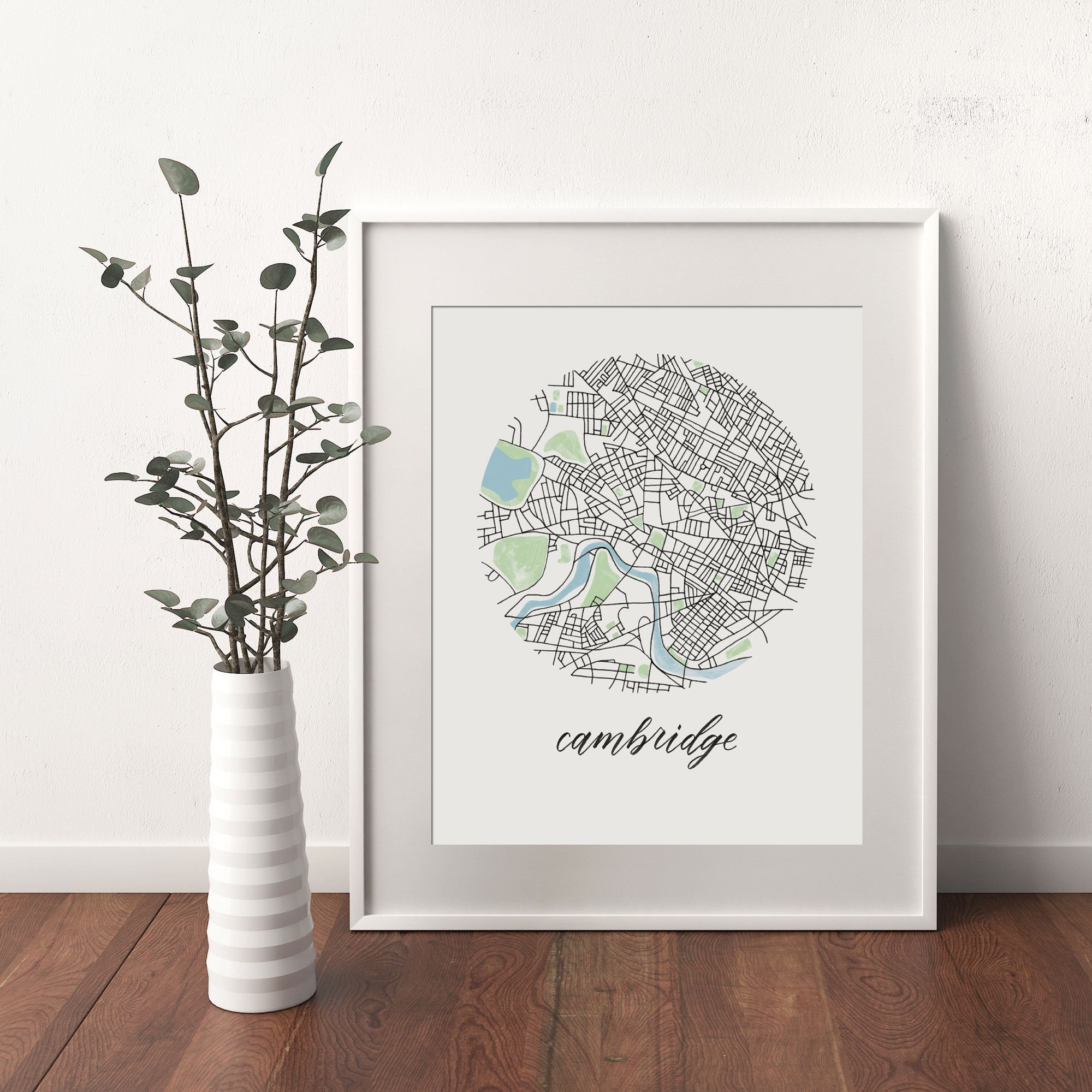 Cambridge, Boston Map print framed and leaning on white wall next to dried leaves in a vase