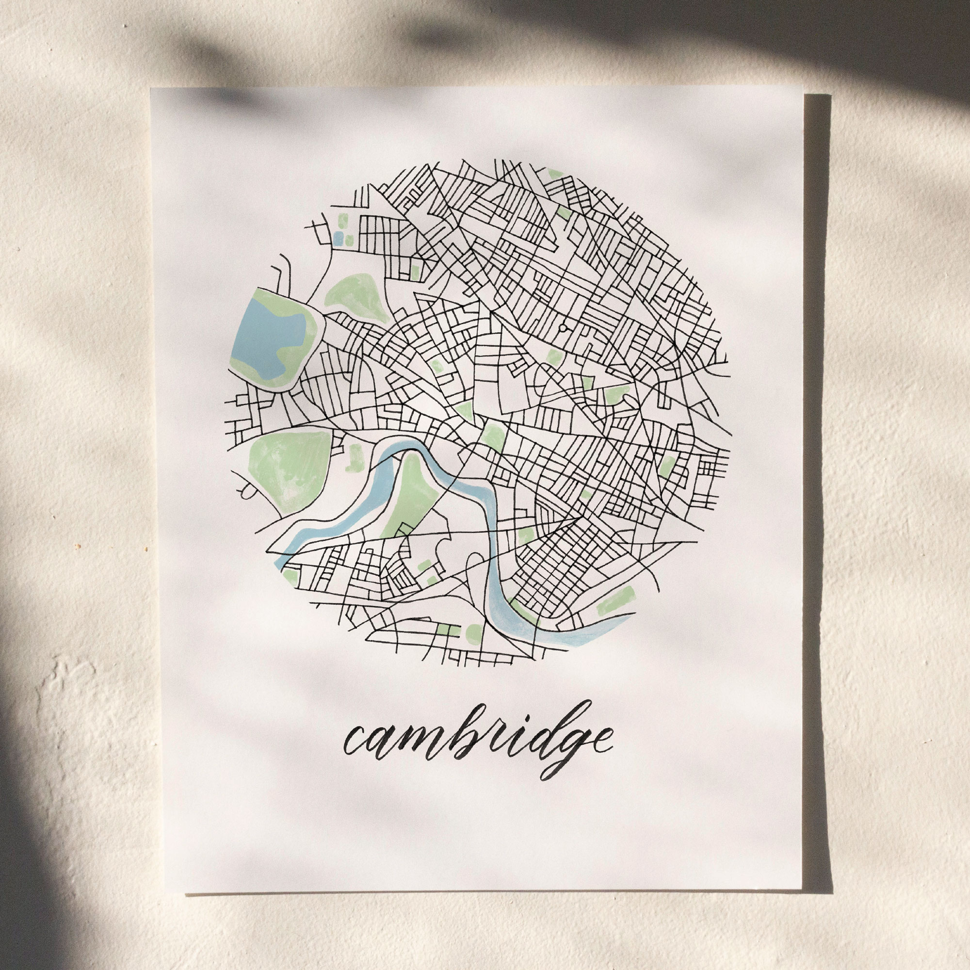 Cambridge, Boston Map Print hanging on white wall with leaf shadows across the image
