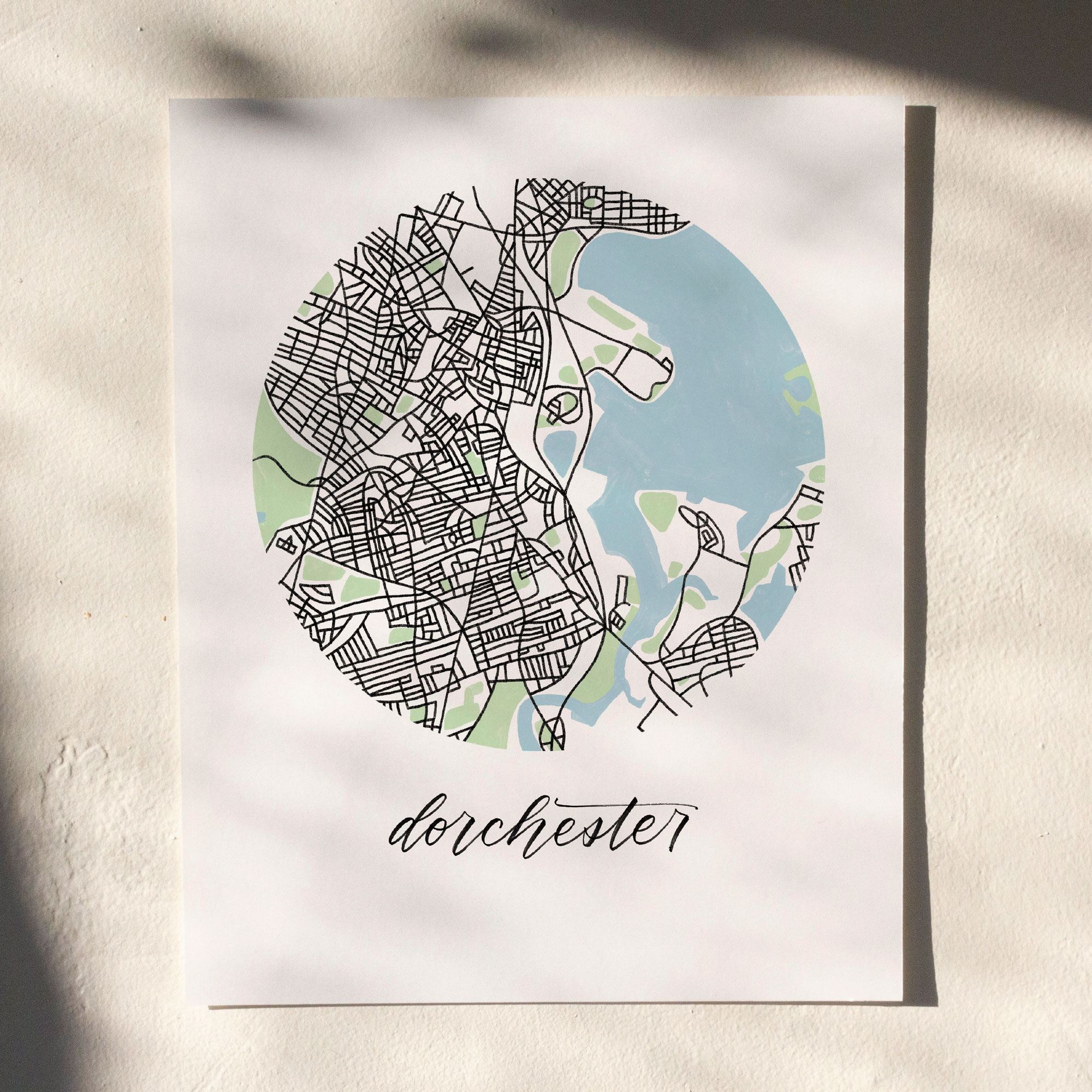 Dorchester, Boston Map Print hanging on white wall with leaf shadows across the image