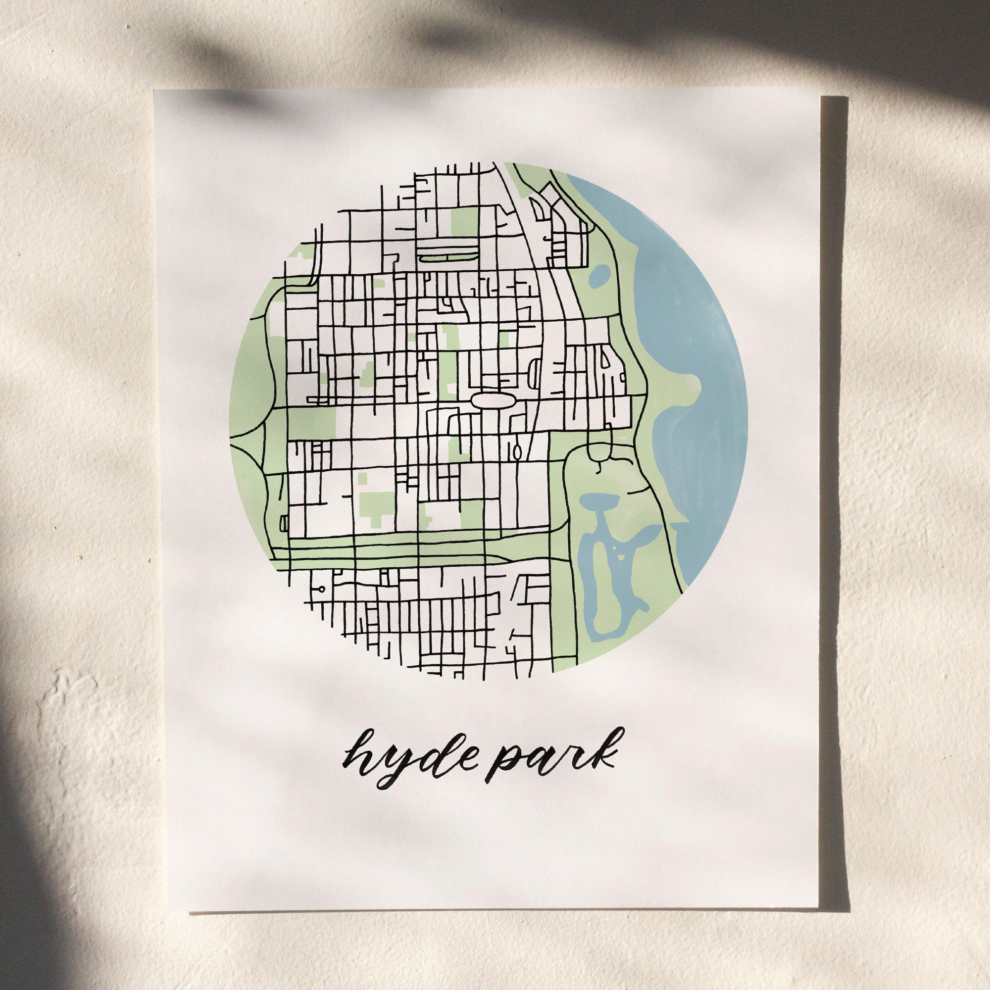 Hyde Park, Chicago Map Print hanging on white wall with leaf shadows across the image