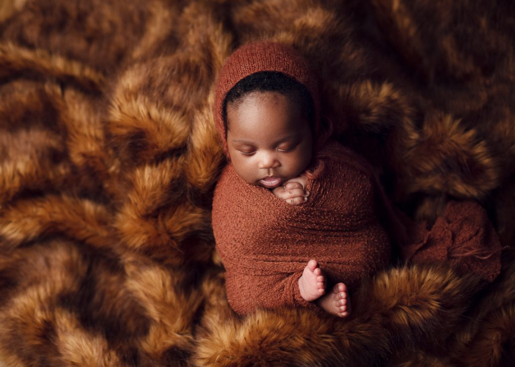 Victoria Newborn photographer BC beautiful baby wrapped in a rust color wrap and nestled cozy in a fluffy faux fur blanket