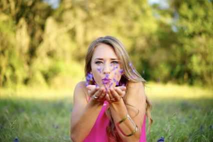 femme qui soufffle sur des pétales de fleur