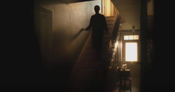 a shadowy dark figure is walking down the stairs in an old house.