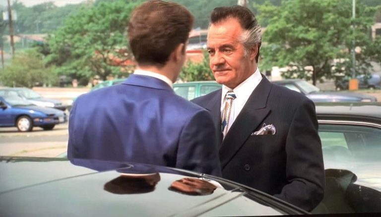 paulie and christopher are standing in the parking lot in modell's wearing suits before christopher's making ceremony.