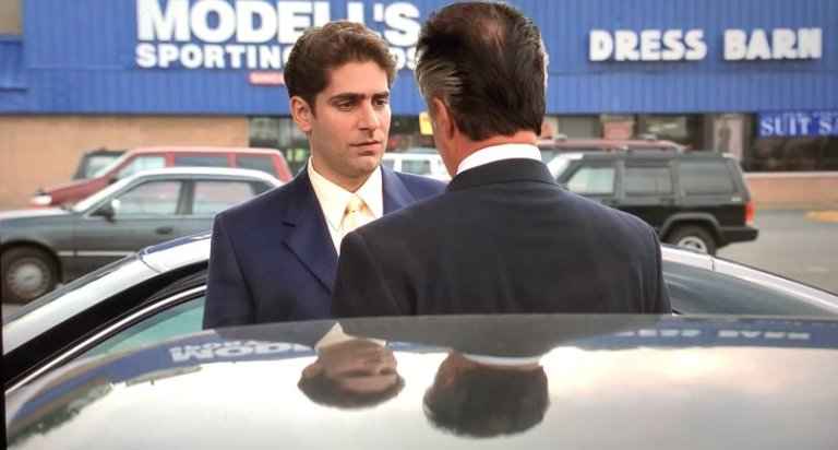 paulie and christopher are standing in the parking lot in modell's wearing suits.