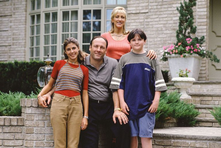 The Sopranos Family taking a photo together in front of their home.