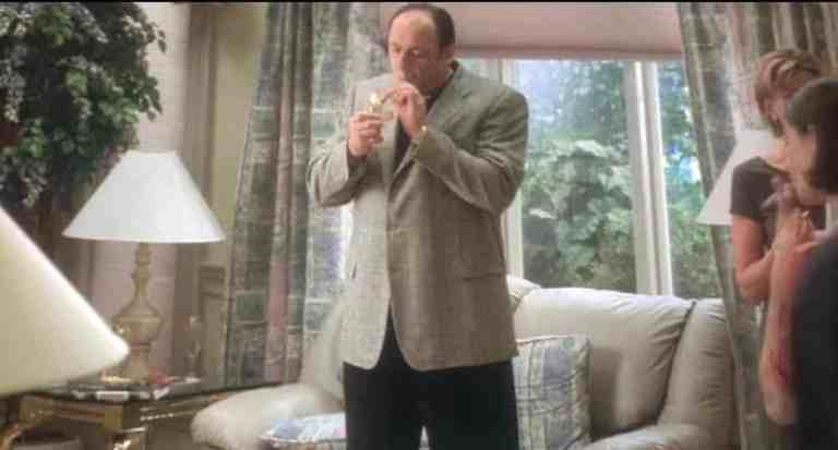 tony soprano is lighting a cigar in the middle of his house during meadow's graduation party.