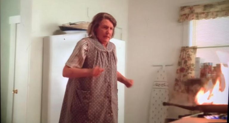 Livia Soprano is scared as she sees there's a fire in her kitchen.