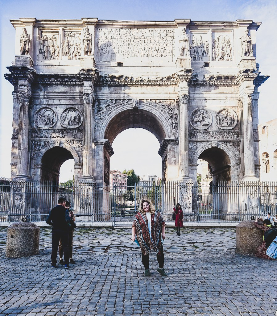Sorcha outside the marble arch of the coliseum in Rome. she is wearing a light blue tunic, and orange patterned chiffon kimono, black leggings and her allbirds. She is Smiling and her hair is down and naturally curly blonde.