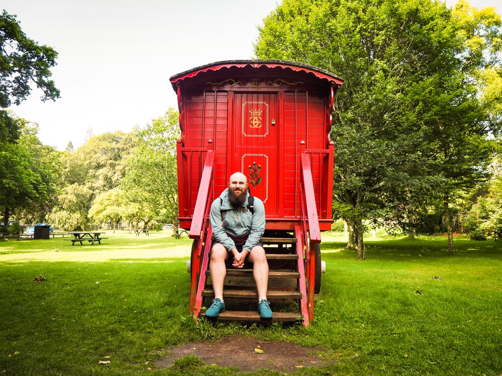 Matthew sitting on the steps of a red gypsy cart in Scotland surrounded by green grass and trees. Wearing shorts, his blue Allbirds and a blue and mulberry jacket.