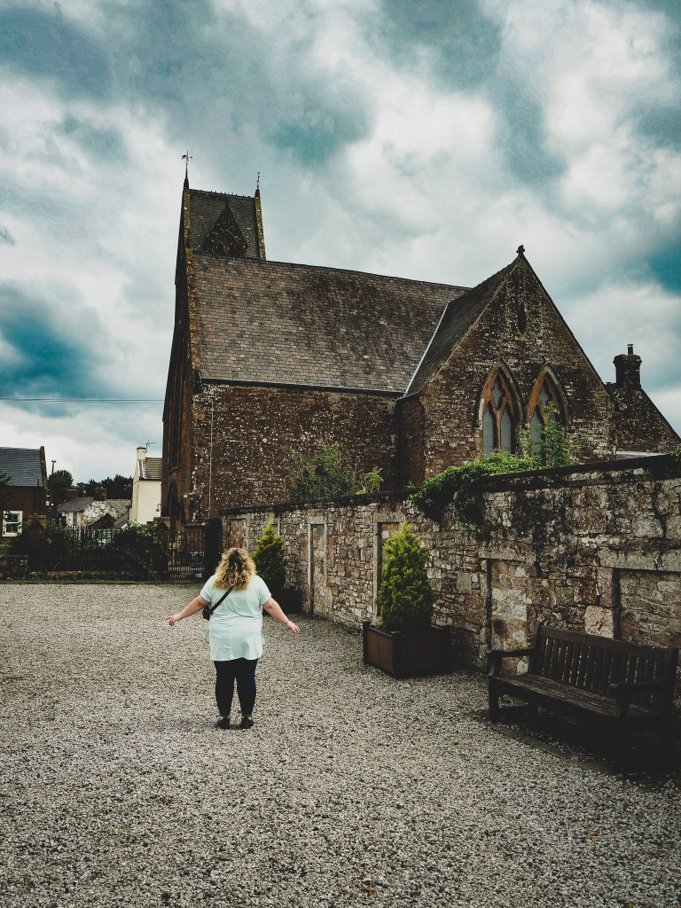 Sorcha outside the church that Thomas Carlyle is buried in in Ecclefeccen Scotland. The church is small and made of stone. Sorcha is wearing a light blue tunic and black leggings and is facing away from the camera.