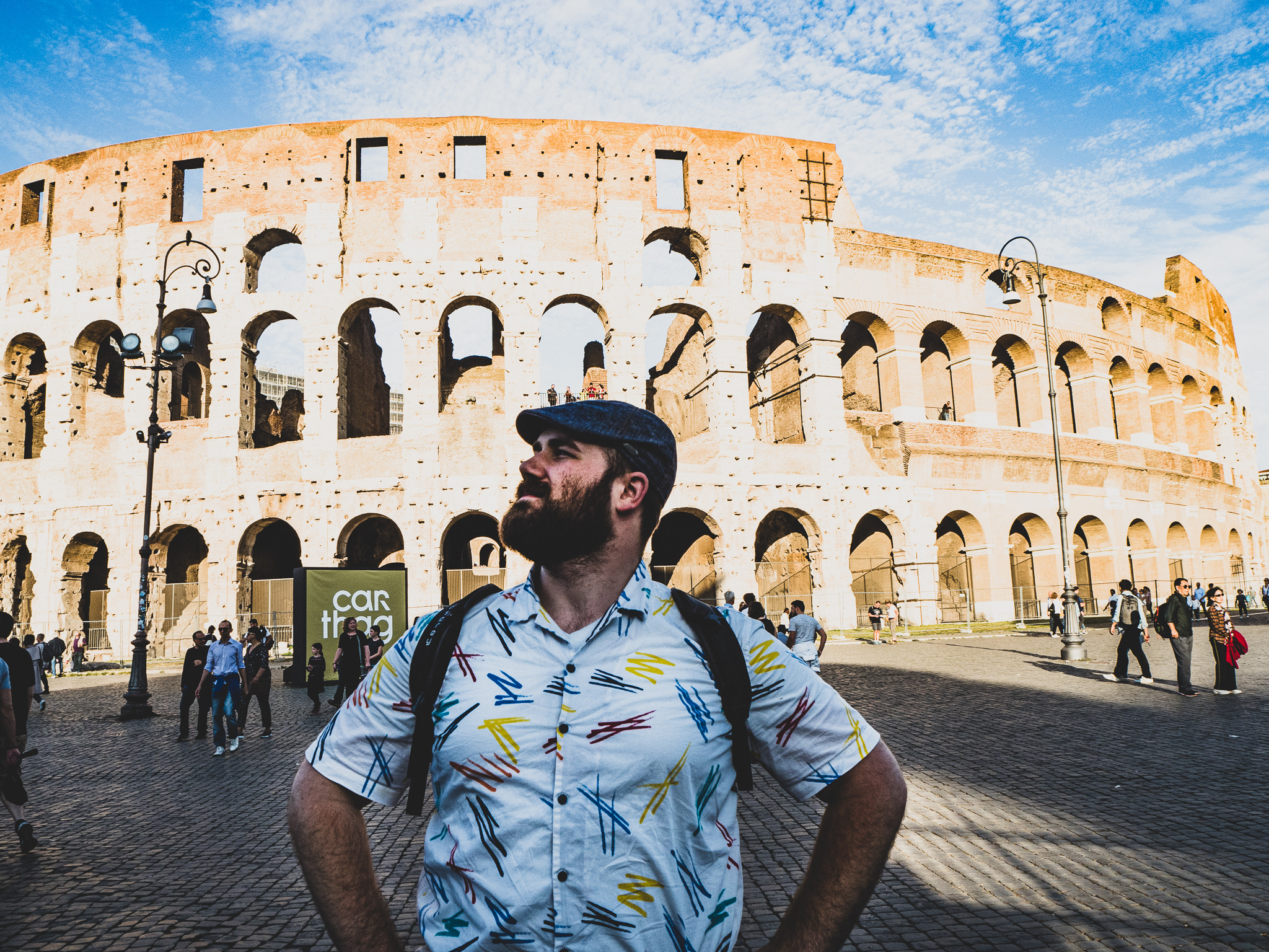 Matthew standing majestically in front of the Coliseum looking outward. He is wearing a white button up shirt with red, blue and yellow squiggles and his Osprey Farpoint Day pack. He has a full beard and is wearing a green tweed driving cap.