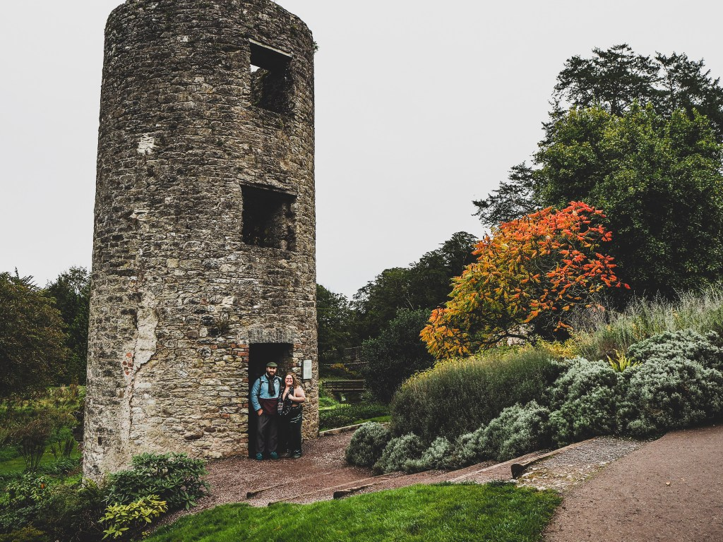 Sorcha And matt standing in front of a large stone cylindrical building called the watchtower. There is a big orange and red coloured tree and lots of diverse greenery around them. They are smiling at the camera and have their arms around each other.
