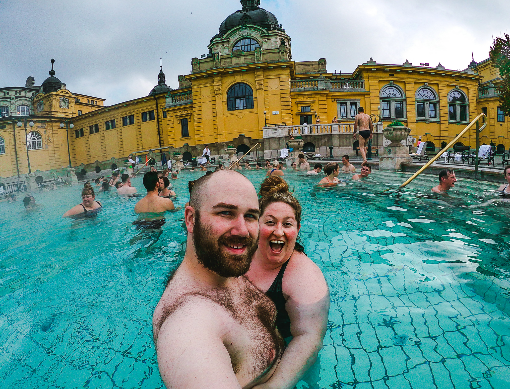 Sorcha and Matt in the outdoor pool at Szechyi Spa in Budapest, the yellow palace juxtaposes the teal tiled heated pool with steam rising around them. Sorcha is wearing a green one piece swim suit and Matt is wearing grey trunks