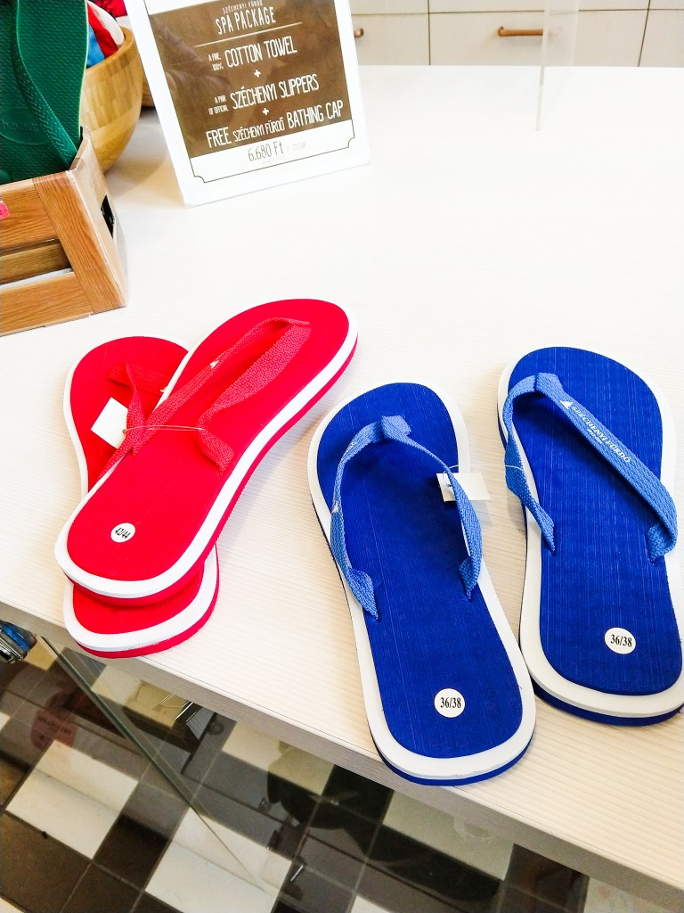 Picture of the flip flops Sorcha and Matt bought at the spa. One red pair and one Blue pair. Sitting on white countertop.