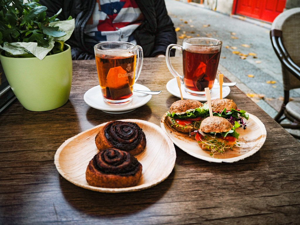 4 white plates on a wooden table with a green flowerpot containing daisies. The two farthest plates contain black tea. the two closest have chocolate rolls and 3 multi-seed buns stuffed with assorted colorful veggies and cheese!