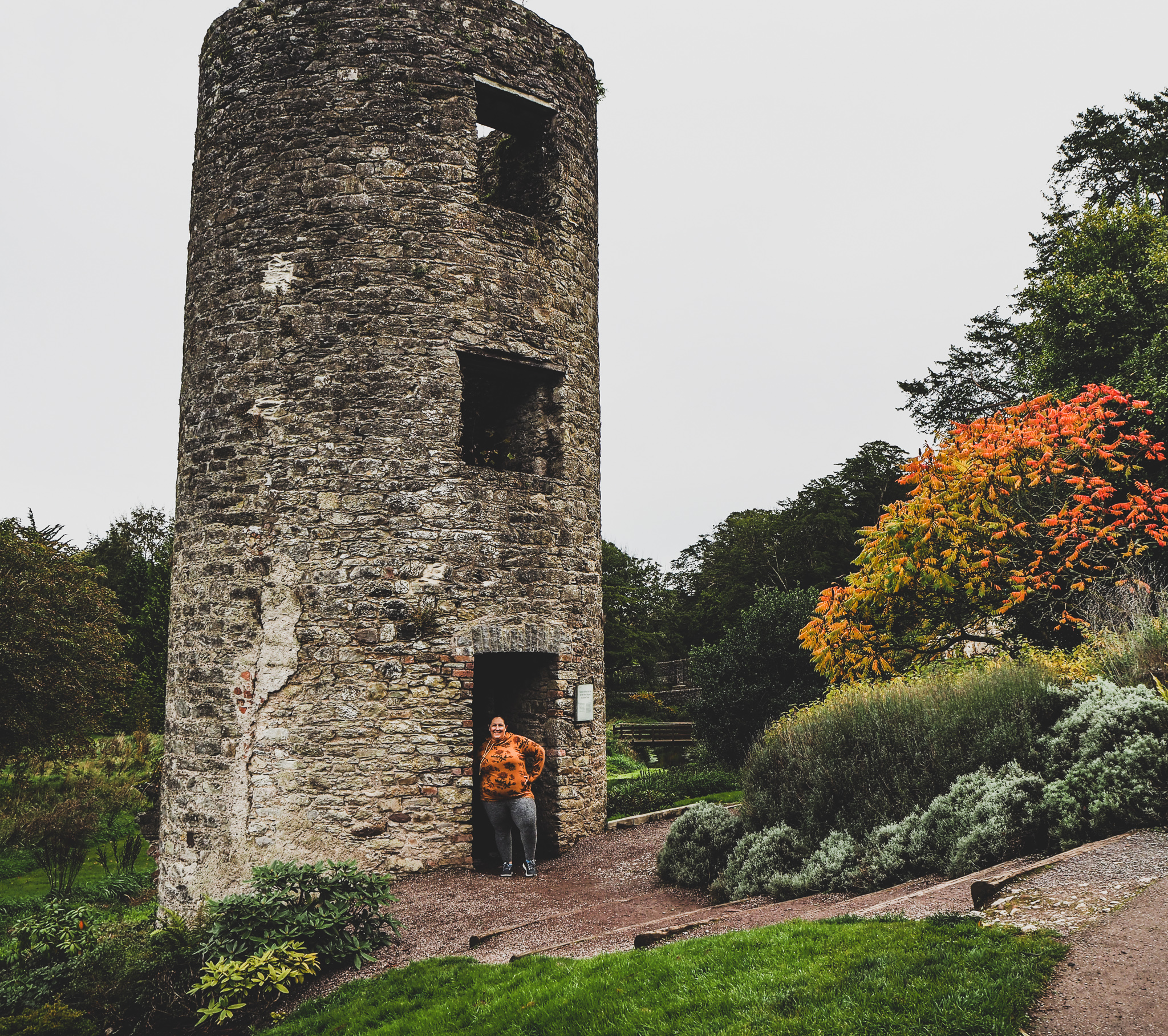picture of Angela at the watchtower in Blarney Castle Gardens, a stone cylinder surrounted by green grass and maple trees