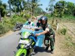 Anggota Babinsa Koramil 0824/20, Koptu Rois Muzaki, membantu seorang warga penjual jamu yang ban motornya mengalami kempes