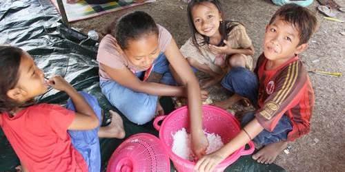Anak-anak makan siang bersama dalam satu tempat (alas kertas) di lokasi pengungsian di Loloan, Lombok Utara