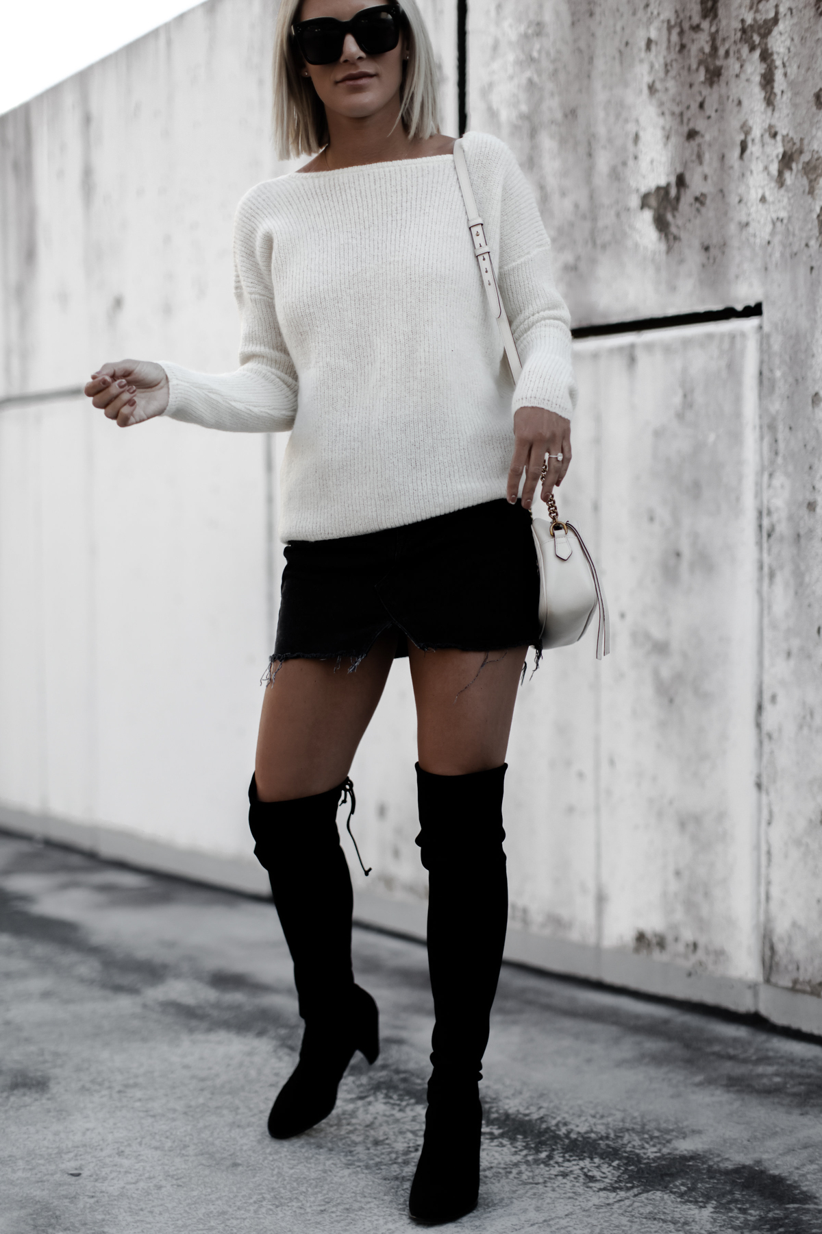 Blogger So Sage in a cream sweater, black skirt, and otk boots