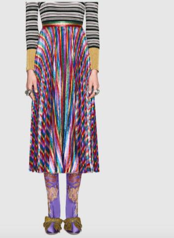 Falda iridiscente estampada de Gucci combinada con una sencilla blusa de rayas.