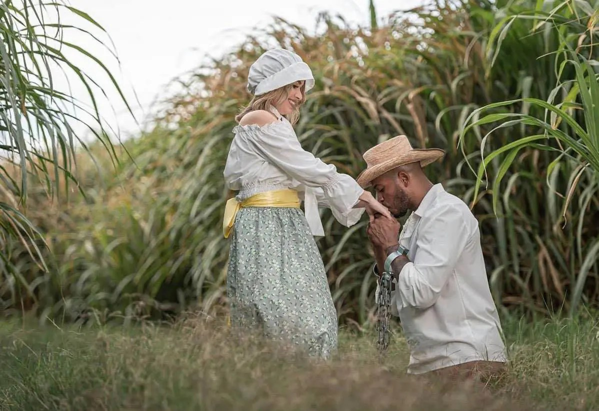 A Black slave kissing a White woman's hand in a field.