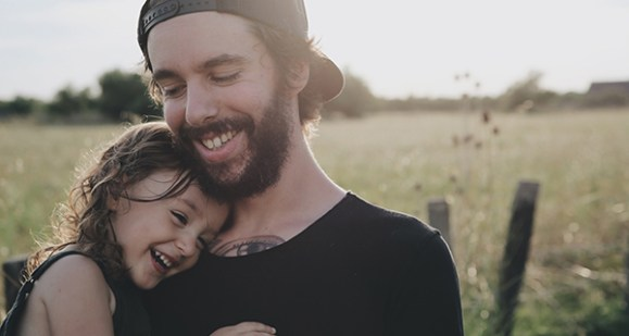 Dad and daughter cuddling and smililng