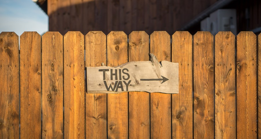 Fence with this way sign