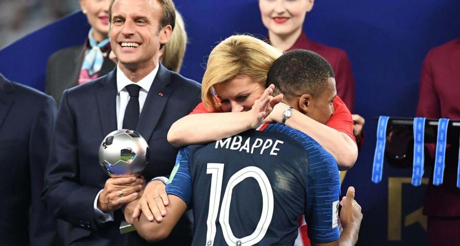 Emmanuel Macron and Kolinda Grabar-Kitarovic hugging Mbappe