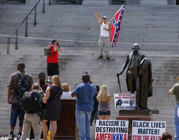 A man gives a Nazi salute on the steps of the capitol as the group says they should not be blamed for the shooting in Charleston, South Carolina, last month when pro-Confederacy Dylann Roof killed nine black people