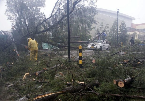 Workers clear the road of fallen trees after strong winds brought by Typhoon Koppu battered Baguio city, north of Manila October 19, 2015. Typhoon Koppu swept across the northern Philippines killing at least nine people as trees, power lines and walls were toppled and flood waters spread far from riverbeds, but tens of thousands of people were evacuated in time. REUTERS/Harley Palangchao - RTS529S