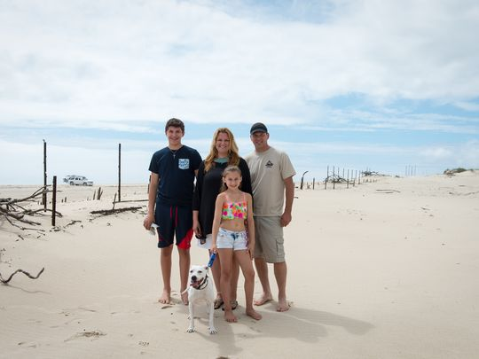 The Berenty's pose for a photo near the dune where they found a message in a bottle with the Indian River Inlet Bridge in the background where the bottle was dropped in the background on Tuesday, May 31.