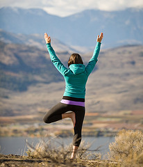 Girl in yoga pose against background of mountains and water