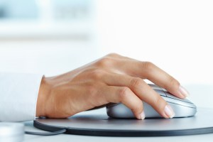 Hand of Black female clicking a silver computer mouse