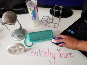 sign, soulcially yours, wireless green speaker, yeti mic, leter steel framed 'J', manicured pink hands on mouse, acer monitor with Asus Laptop