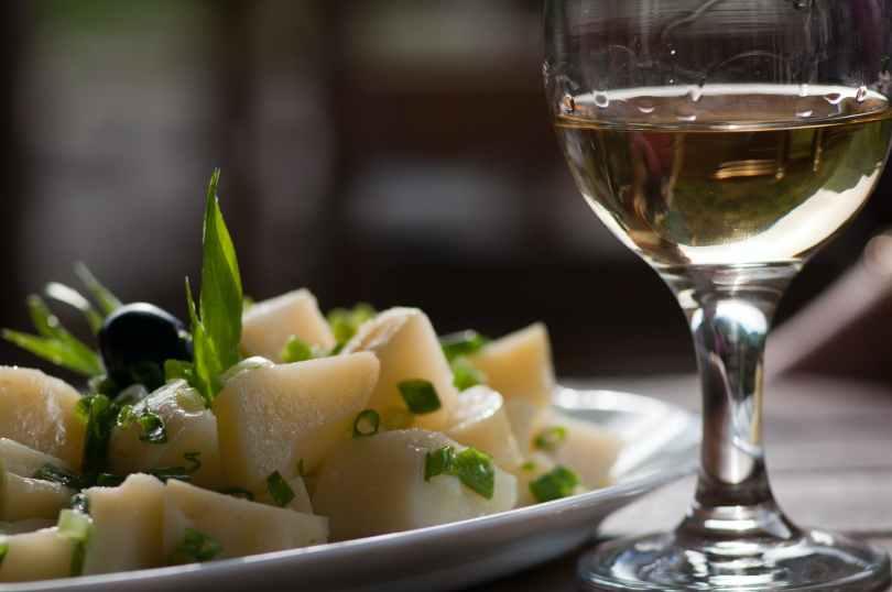 glass of wine near steamed sliced potato dish