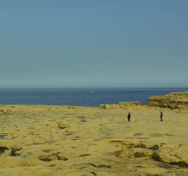 Two women walking around flat cliffs with a view of the ocean behind