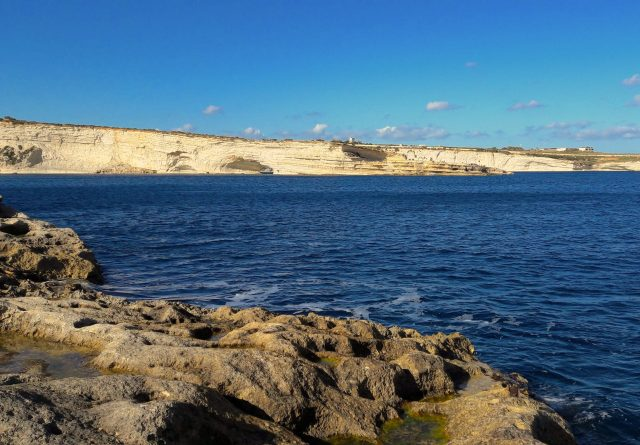The Mediterranean sea with a long cliffside in the distance