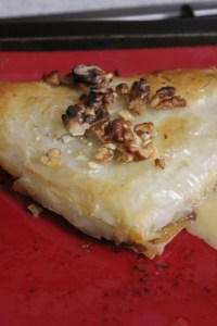 Brush with butter and sprinkle with walnuts. Bake until golden brown.