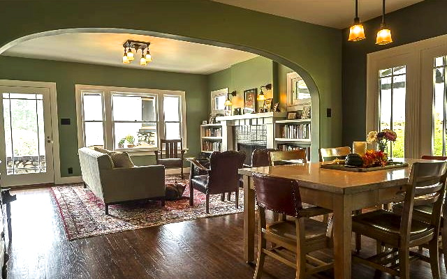 Open living space with original wood floors, fireplace and built-ins