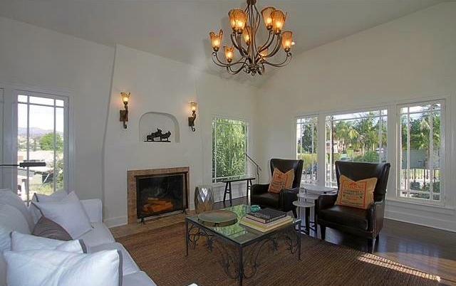 Living room with Batchelder fireplace, barreled ceiling and original wood floors