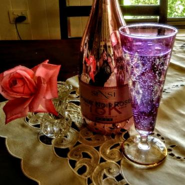 close up of bottle, rose and glass