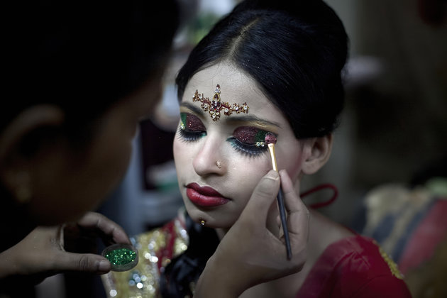 """MANIKGANJ, BANGLADESH - AUGUST 20: 15 year old Nasoin Akhter has her makeup done at a beauty parlour on the day of her wedding to a 32 year old man, August 20, 2015 in Manikganj, Bangladesh.  In June of this year, Human Rights Watch released a damning report about child marriage in Bangladesh. The country has one of the highest rates of child marriage in the world, with 29% of girls marrying before the age of 15, and 65% of girls marrying before they turn 18. The detrimental effects of early marriage on a girl cannot be overstated. Most young brides drop out of school. Pregnant girls from 15-20 are twice as likely to die in childbirth than those 20 or older, while girls under 15 are at five times the risk. Research cites spousal age difference as a significant risk factor for violence and sexual abuse. Child marriage is attributed to both cultural tradition and poverty. Parents believe that it """"protects"""" girls from sexual assault and harassment. Larger  dowries are not required for young girls, and economically, women's earnings are insignificant as compared to men's. (Photo by Allison Joyce/Getty Images)"""