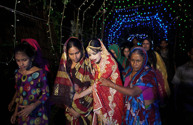 """MANIKGANJ, BANGLADESH - AUGUST 20: 15 year old Nasoin Akhter is led by relatives to a car that will take her to her new home on the day of her wedding to a 32 year old man, August 20, 2015 in Manikganj, Bangladesh.  In June of this year, Human Rights Watch released a damning report about child marriage in Bangladesh. The country has one of the highest rates of child marriage in the world, with 29% of girls marrying before the age of 15, and 65% of girls marrying before they turn 18. The detrimental effects of early marriage on a girl cannot be overstated. Most young brides drop out of school. Pregnant girls from 15-20 are twice as likely to die in childbirth than those 20 or older, while girls under 15 are at five times the risk. Research cites spousal age difference as a significant risk factor for violence and sexual abuse. Child marriage is attributed to both cultural tradition and poverty. Parents believe that it """"protects"""" girls from sexual assault and harassment. Larger  dowries are not required for young girls, and economically, women's earnings are insignificant as compared to men's. (Photo by Allison Joyce/Getty Images)"""